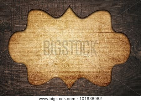 Dark brown ornate wooden frame, fretwork on old scratched cutting board