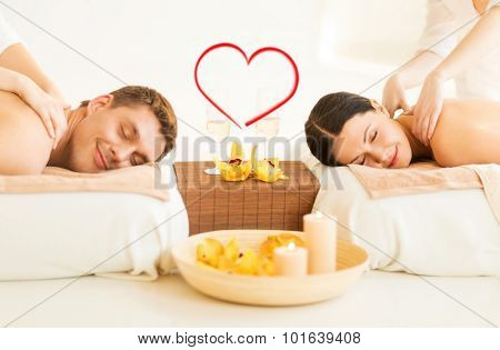 spa, beauty, love and happiness concept - smiling couple with candles, flowers and champagne glasses getting massage in spa salon
