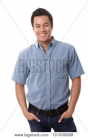 Casual young man in shirt and jeans smiling happy, standing with hands in pockets.
