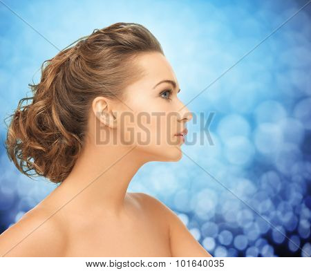 health, people and beauty concept - beautiful young woman face over blue holidays lights background