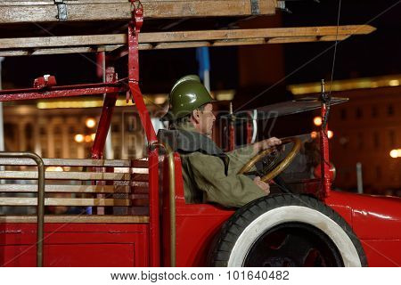 ST. PETERSBURG, RUSSIA - SEPTEMBER 7, 2015: Actor in historic costume in the retro fire truck during the opening ceremony of XI World Championship in Fire and Rescue Sport