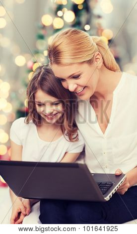 family, childhood, holidays, technology and people - smiling mother and little girl with laptop computer over christmas tree lights background