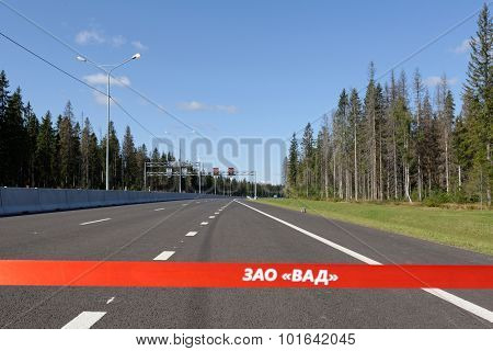 NOVOPRIOZERSK HIGHWAY, LENINGRAD OBLAST, RUSSIA - SEPTEMBER 11, 2015: Red ribbon across the road during the opening of new stretch of Novopriozersk highway. Construction began in 2013