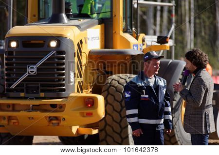 NOVOPRIOZERSK HIGHWAY, LENINGRAD OBLAST, RUSSIA - SEPTEMBER 11, 2015: Participant of grader competitions talks with press during the final of Worldskills Russia championship among road workers