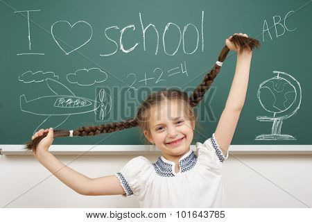 girl with pigtail drawing object on school board