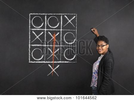 South African Or African American Woman Teacher Writing Tic Tac Toe On Chalk Black Board Background
