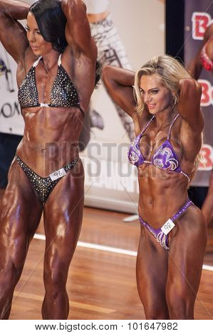Female Bodybuilders In Abdominals And Thighs Pose