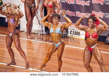 Three Female Bodybuilders In Front Double Biceps Pose And Bikini