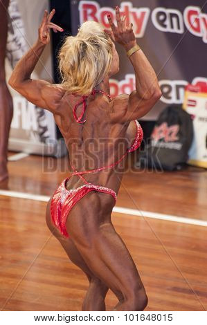 Female Bodybuilder In Back Double Biceps Pose And Red Bikini