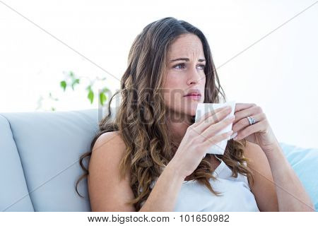 Sad woman sitting on sofa at home