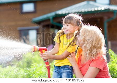 Little gardener girl with mother watering on lawn near house
