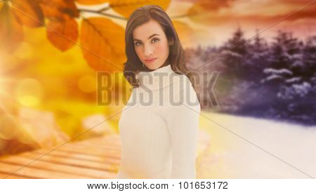Pretty brunette in white jumper posing against autumn changing to winter
