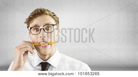 Geeky businessman biting a pencil against grey wall