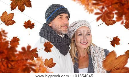Cheerful couple in warm clothing against autumn leaves