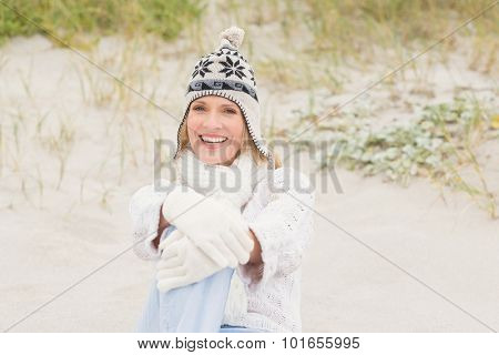 Woman sitting down on the sand at the beach