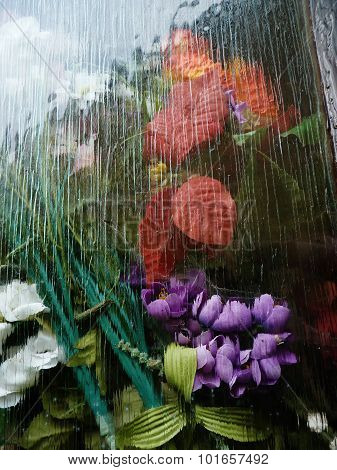 faux flowers behind glass textured abstract