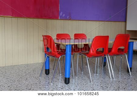 Kindergarten Classroom With Desks And Red Chairs