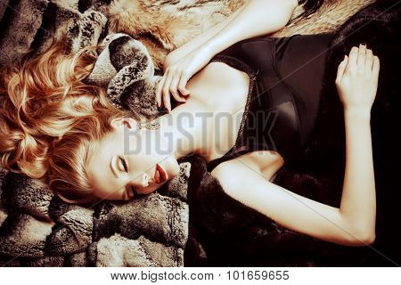 Stunning young woman with beautiful blonde hair lying on furs. Luxury, rich lifestyle. Jewellery. Fashion shot.