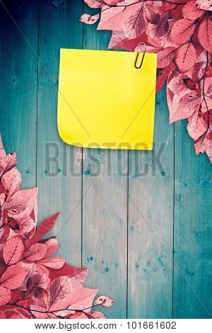 Sticky note with grey paperclip against autumn leaves pattern