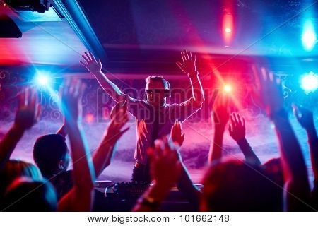 Energetic deejay with headphones having fun by turntables in front of dancing crowd