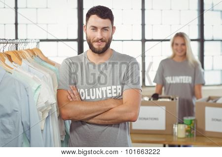 Portrait of happy man with arms crossed standing by clothes rack in office