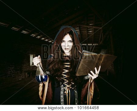 Beautiful Young Halloween Witch Reading Magical Book And Holding
