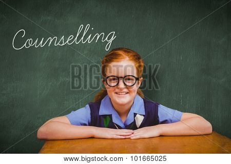 The word counselling and smiling pupil against green chalkboard