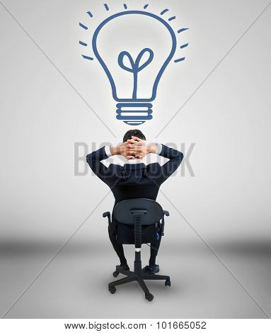 Young business man looking at bulb on wall