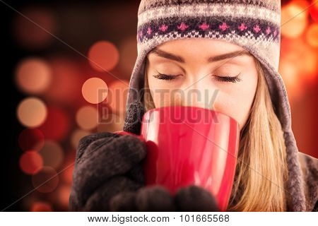 Happy blonde in winter clothes holding mug against light circles on black background