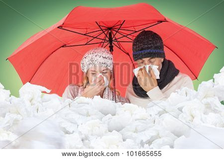 Ill couple sneezing in tissue while standing under umbrella against green vignette