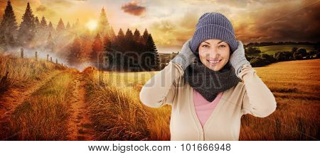Smiling brunette wearing warm clothes against country scene