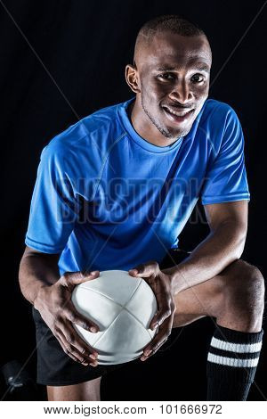 Portrait of rugby player with ball smiling while kneeling against black background