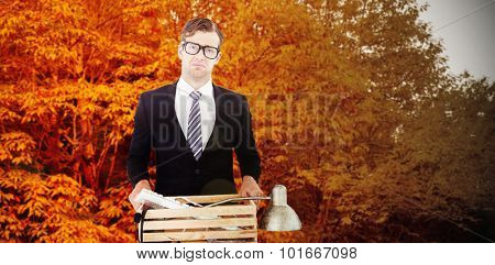 Sad geeky businessman holding box of his things against autumn scene