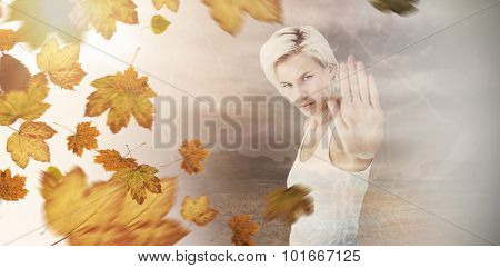 Angry pretty blonde showing her hand against autumn leaves