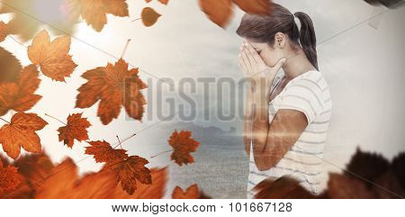 Side view of upset woman covering face against autumn leaves