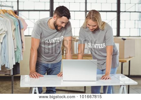 Volunteers discussing while working on laptop in creative office