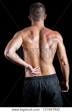 Rear view of shirtless athlete with back pain against black background