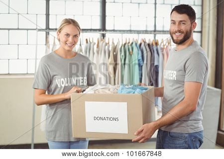 Portrait of smiling volunteer holding clothes donation box in office