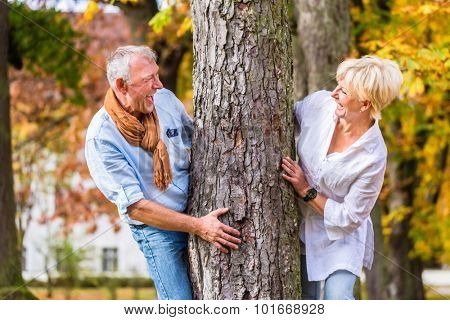 Couple, senior man and woman, flirting with each other playing hide and seek around a tree in fall tree