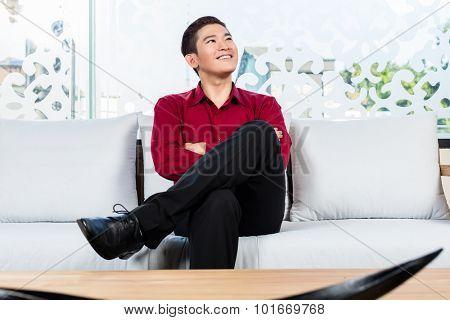 Asian Korean man sitting on sofa in furniture store