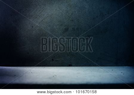 Basement like concrete wall and floor in dark bluish light.