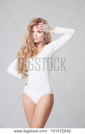 Sexy blonde woman with beautiful long curly hair in white bodysuit