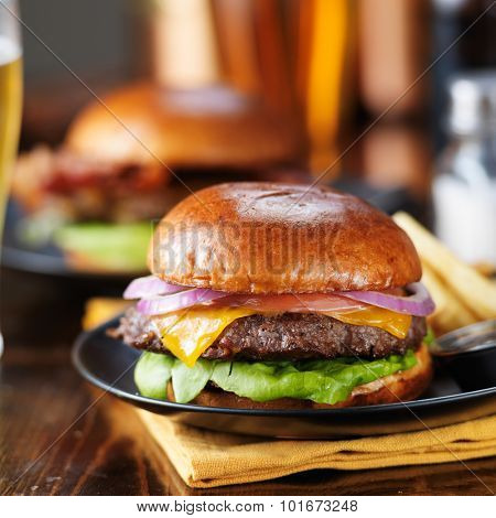 cheeseburgers and fries on table top with onion, tomato, lettuce and cheese