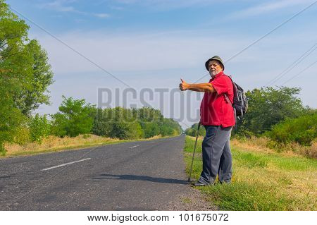 Senior hitchhiker standing on a roadside in Ukraine