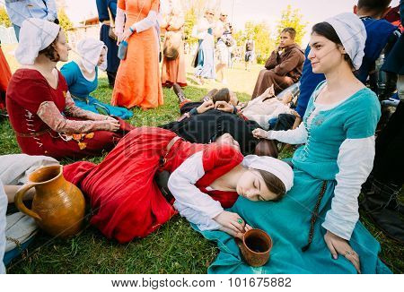 Participants of festival of medieval culture resting in shadow t