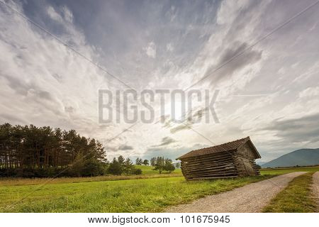 old oblique wooden shed house in meadow at dusk