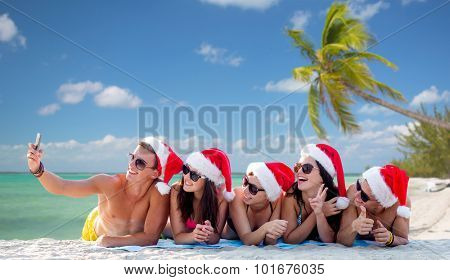summer vacation, holidays, technology, travel and people concept - group of friends in santa helper hats taking selfie with smartphone on beach