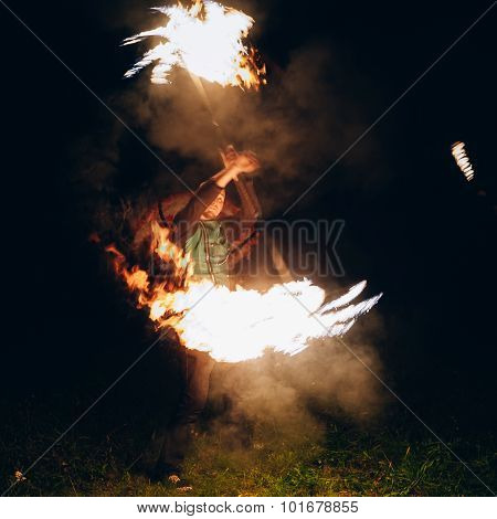 Fire Show at night. Man stands in front of an audience with a bu