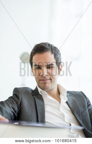 Young Business Manager Sitting At His Office Desk Frowning Upon A Document