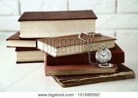 Pocket clock and vintage books, on light wall background